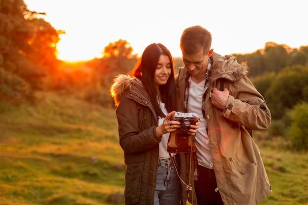 自然の中を散歩を楽しんでいるロマンチックな若いカップル