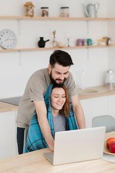 ロマンチックな若いカップルを抱き締めるとノートパソコンを見て