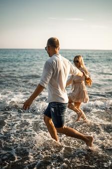 Романтическая молодая влюбленная пара вместе гуляет по песку вдоль пляжа средиземного моря. летний отдых в теплой стране. выборочный фокус