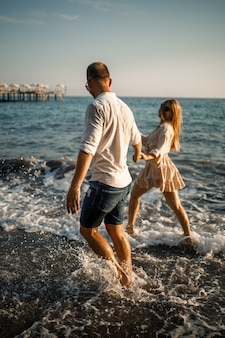 Романтическая молодая влюбленная пара вместе гуляет по песку вдоль пляжа средиземного моря. летний отдых в теплой стране.