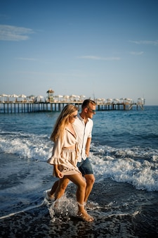 모래에 함께 사랑에 빠진 로맨틱 젊은 부부는 지중해 해변을 따라 산책합니다. 따뜻한 나라의 여름 휴가.