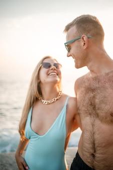 지중해 해변을 따라 석양에 함께 걷는 사랑에 로맨틱 젊은 부부. 따뜻한 나라에서 여름 휴가입니다. 터키에서 휴가를 보내는 행복한 부부. 선택적 초점