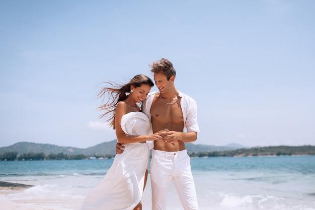 해변에서 여름 휴가를 즐기는 흰 옷에 로맨틱 젊은 부부