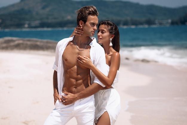 ビーチで夏休みを楽しんでいる白い服を着たロマンチックな若いカップル