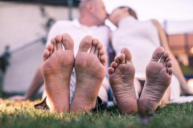 ロマンチックな若いカップルが庭でキスします。フォーカスの家族の足。公園の芝生の上で横になっている若いカップルの足。