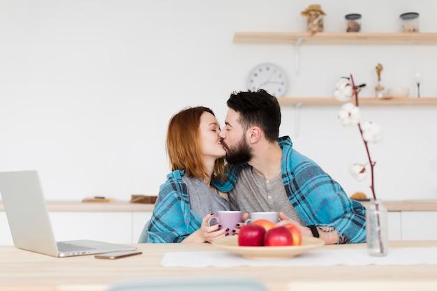 ロマンチックな若いカップルが台所でキス
