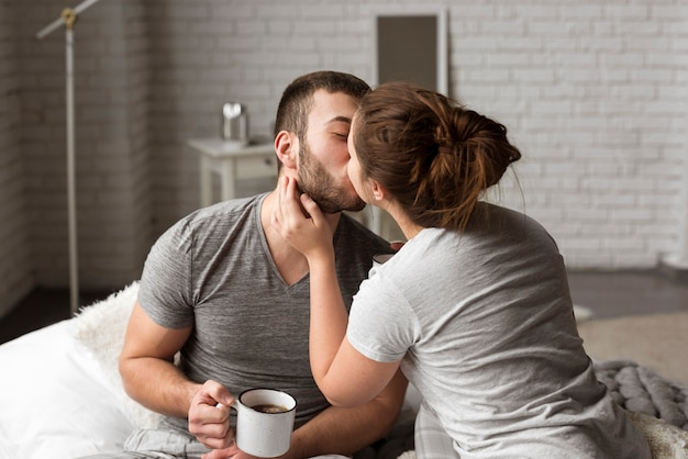 Romantic young couple kissing indoors