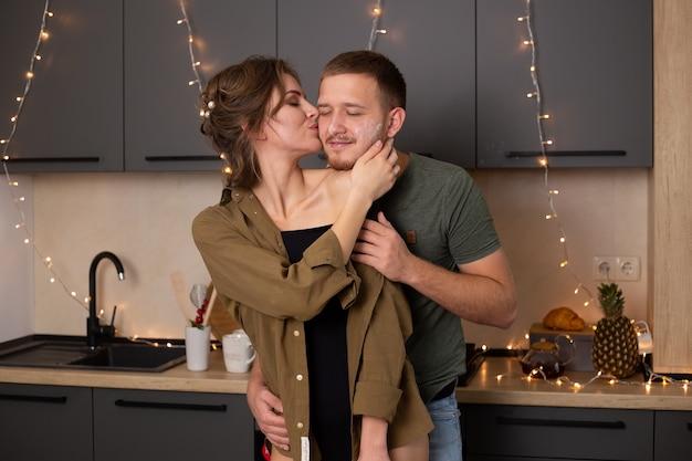 ロマンチックな若いカップルがキッチンで一緒に料理をしながらキスし、一緒に素晴らしい時間を過ごします。