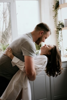 Romantic young couple in the kitchen. the girl in the white shirt.