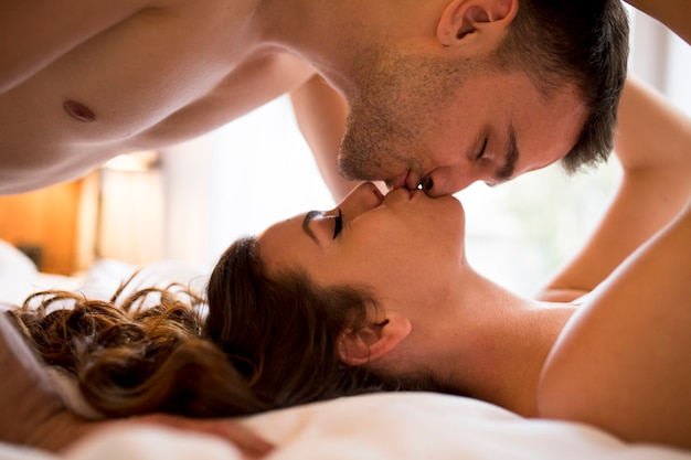 Romantic young couple laying on the bed with bodies in opposite directions while kissing