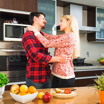 Romantic young couple looking at each other in the kitchen