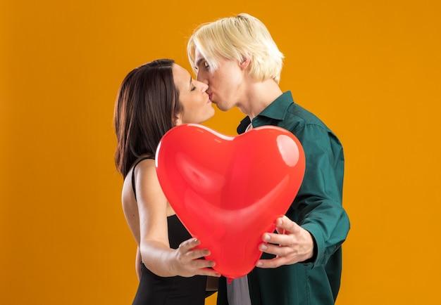 プロフィールビューに立っているバレンタインデーのロマンチックな若いカップルは、コピースペースのあるオレンジ色の壁に隔離された目を閉じてキスするハート型の風船を伸ばします。