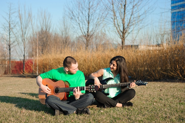 Romantic young couple portrait playing guitar under blue sky,