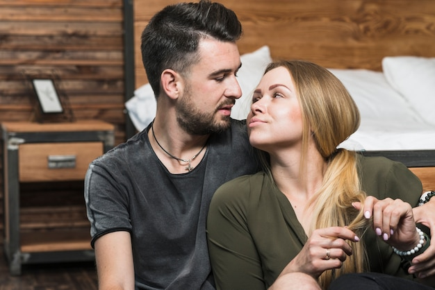 Romantic young couple sitting in bedroom looking at each other