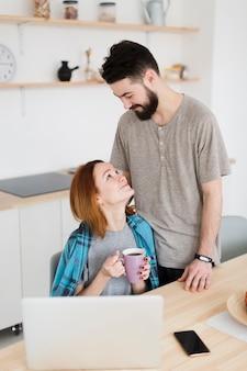 ロマンチックな若いカップルが台所で時間を過ごす
