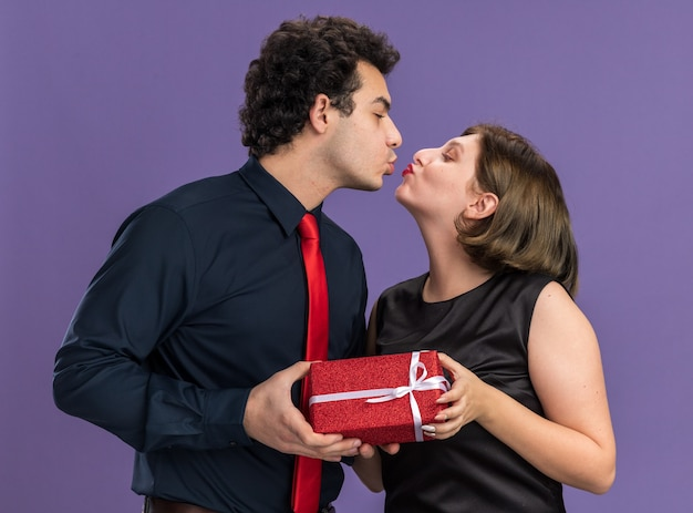 Romantic young couple on valentine's day man giving gift package to woman both looking at each other kissing isolated on purple wall