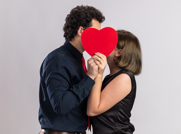 Romantic young couple on valentine's day standing in profile view holding heart shape kissing behind it isolated on white wall