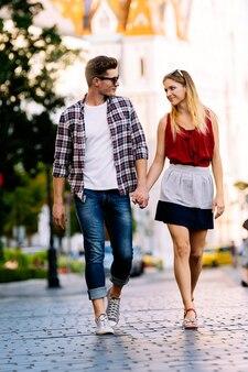 街を歩くロマンチックな若いカップル。関係の概念。