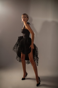 Romantic young female in short festive black evening dress posing on gray studio background with copy space for ad