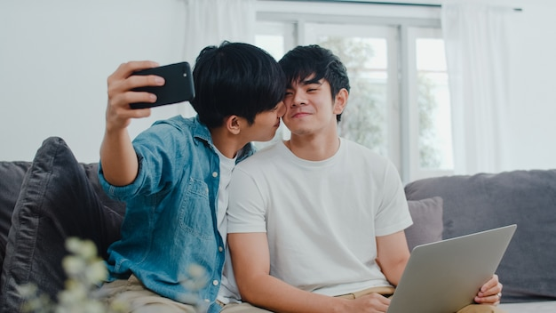 Romantic young gay couple funny selfie by cellphone at home. asian lover lgbt male happy relax fun using technology mobile phone smiling take a photo together while lying sofa in living room .