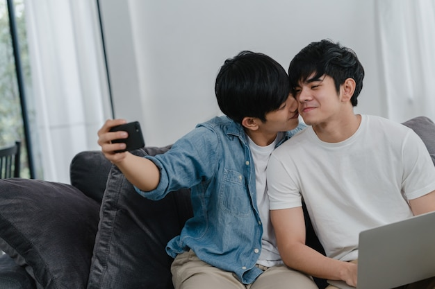 Romantic young gay couple funny selfie by cellphone at home. asian lover male happy relax fun using technology mobile phone smiling take a photo together while lying sofa in living room .