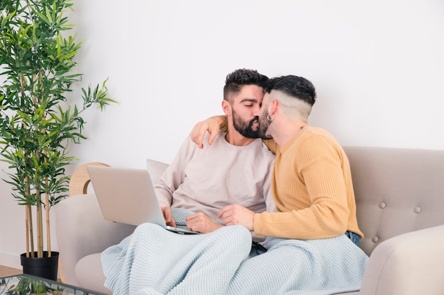 Romantic young gay couple sitting on sofa kissing each other