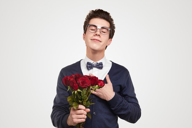 Romantic young gentleman in elegant outfit and spectacles with red roses keeping hand on chest while dreaming about date against white background