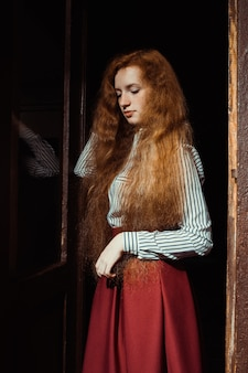 Romantic young ginger model with lush red hair and freckles standing at the old doors