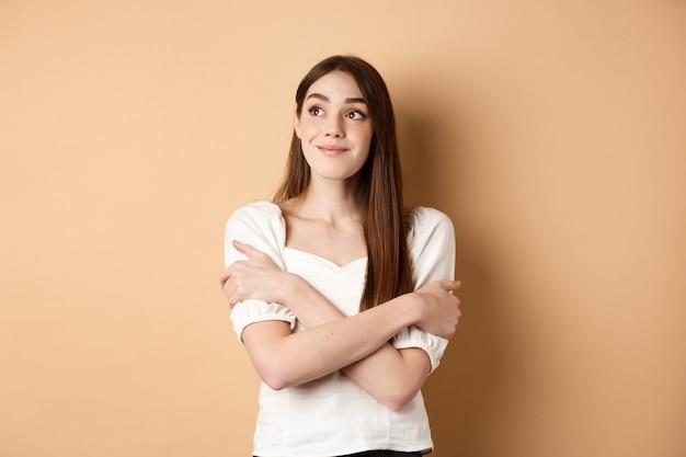 夢を見て、抱きしめ、左上隅で微笑んで、ベージュの背景の上に立って、素敵な何かをイメージしているロマンチックな若い女の子。