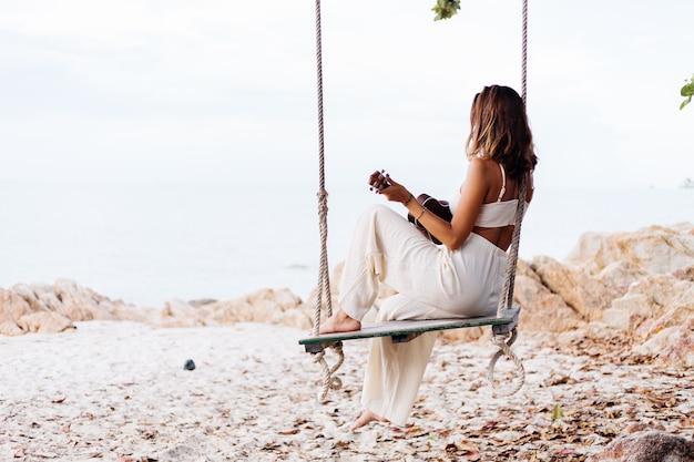 日没時の熱帯の岩のビーチでウクレレとロマンチックな若い幸せな穏やかな白人女性