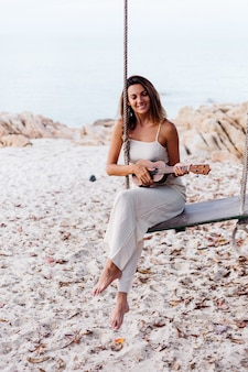 Romantic young happy calm caucasian woman with ukulele on tropical rocky beach at sunset