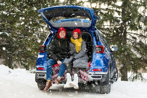 Romantic young hipster couple hugging while sitting in car trunk. love, valentines day