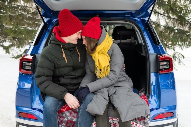 Романтичная молодая пара битника обнимая пока сидя в багажнике автомобиля. любовь, валентинки и праздник