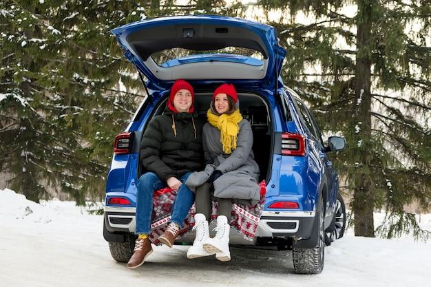 Романтичная молодая пара битника обнимая пока сидя в багажнике автомобиля. любовь, день святого валентина