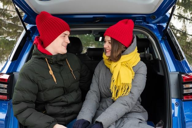 Романтическая пара молодых хипстеров обниматься, сидя в багажнике автомобиля