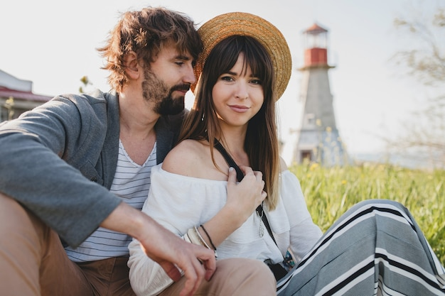 Romantic young hipster couple indie style in love walking in countryside, lighthouse on background, summer vacation