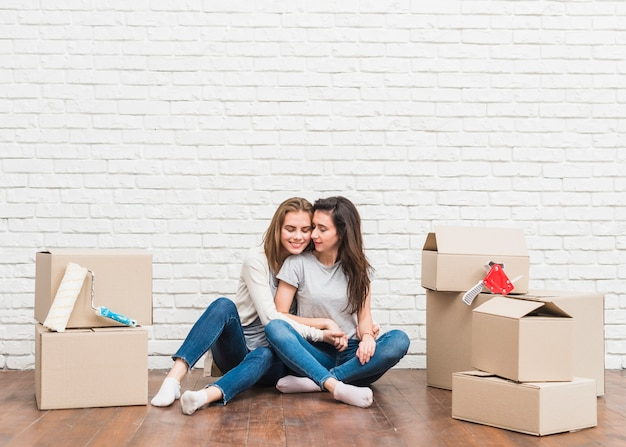 Romantic young lesbian couple sitting between the moving cardboard boxes in apartment