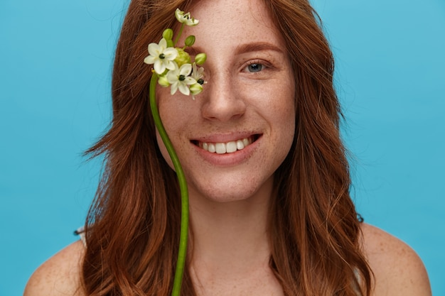 Romantic young lovely redhead woman with curls showing her pleasant emotions and smiling pleasantly at camera, standing over blue background with naked shoulders