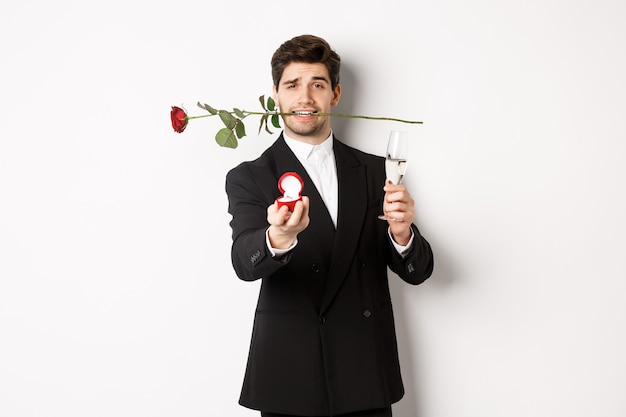 Romantic young man in suit making a proposal, holding rose in teeth and glass of champagne, showing engagement ring, asking to marry him, standing against white background.