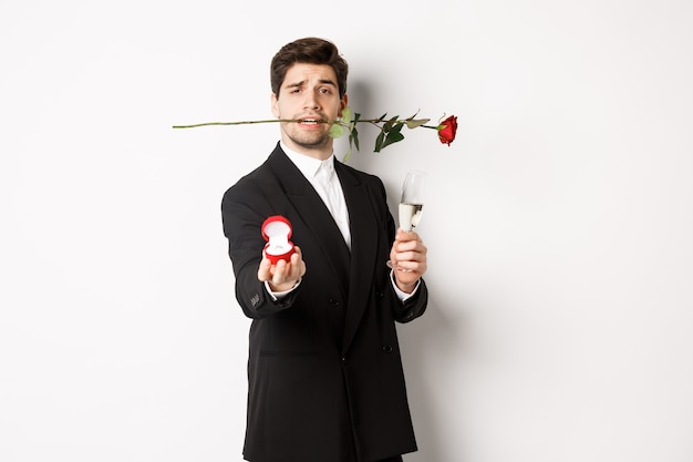 Romantic young man in suit making a proposal, holding rose in teeth and glass of champagne, showing engagement ring, asking to marry him, standing against white background