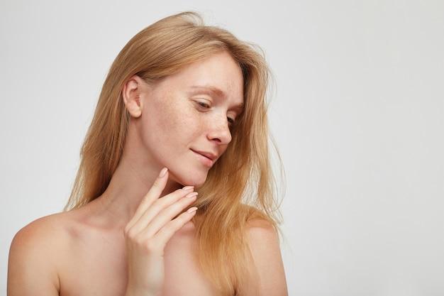 Романтическая молодая красивая рыжая женщина с длинными волосами, касающаяся подбородка поднятой рукой и мягко улыбаясь, стоящая у белой стены