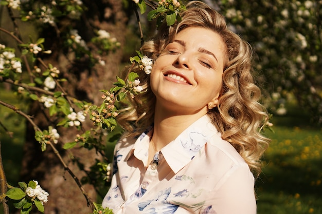 Romantic young woman in the spring garden among apple blossom. beautiful woman, happy spring