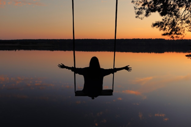 Romantic young woman on a swing over lake at sunset. young girl traveler sitting on the swing in beautiful nature, view on the lake