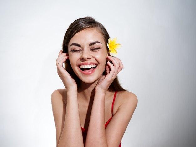 밝은 배경 미소 웃음 감정에 그녀의 머리에 꽃과 함께 낭만적 인 젊은 여자