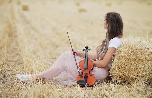 필드에서 그녀의 손에 바이올린을 들고 흐르는 머리와 낭만적 인 젊은 여자