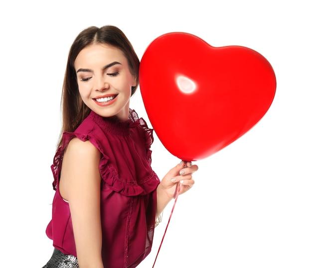 白のバレンタインデーのハート型の風船を持つロマンチックな若い女性