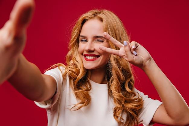 Giovane donna romantica con manicure alla moda in posa sulla parete rossa. adorabile signora dai capelli biondi che ride
