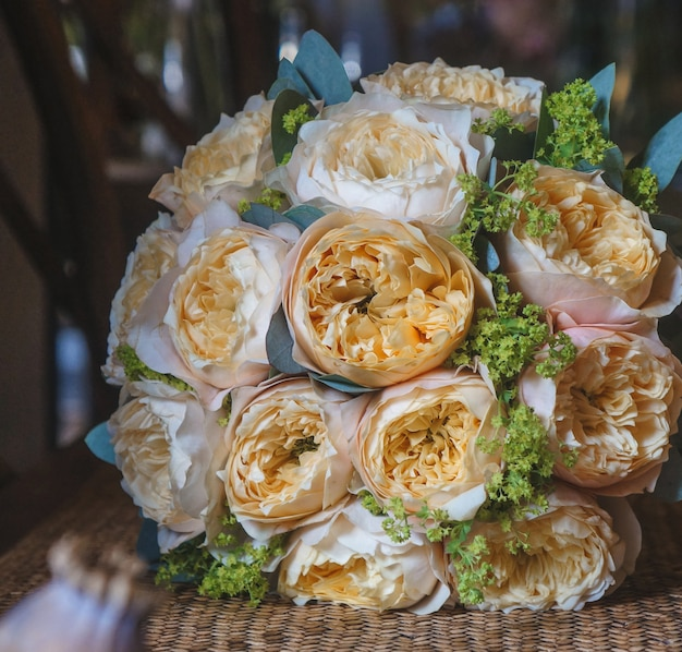 A romatic bridal bouquet of coral peonies standing on a bamboo table