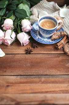 Romatic coffee in a cup on a wooden background with a plaid, a bouquet of white roses and autumn coziness. good morning. upper view. copy spase