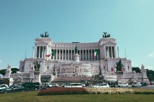 이탈리아 로마 - 2018년 7월 3일: 로마의 베네치아 광장에 있는 비토리오 에마누엘레 2세 기념비(vittoriano or altare della patria)라고도 알려진 박물관의 전경. 여름날과 푸른 하늘